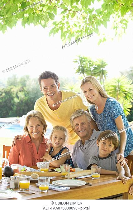 Multi-generation family at breakfast table outdoors