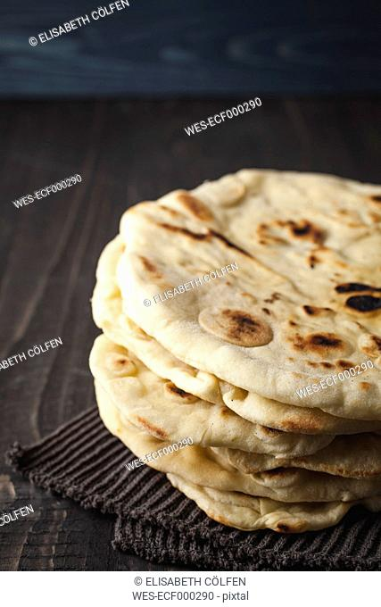 Stack of flat breads on wooden table, close up