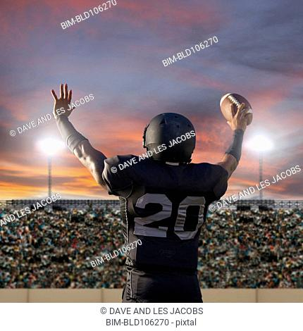African American football player holding ball