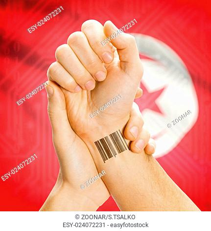 Barcode ID number on wrist and national flag on background - Tunisia