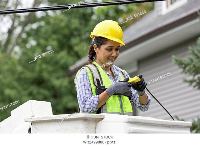 Hispanic female cable lineman stripping cable in the rain