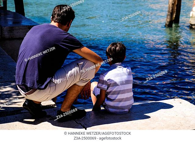 Dad and child watching the water in Venice, Italy Europe