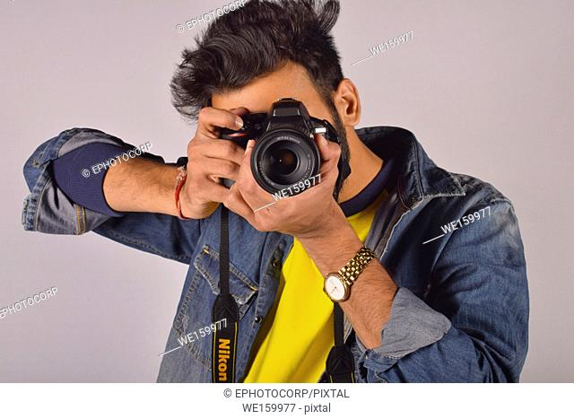 Young male model posing with professional camera, Pune, Maharashtra
