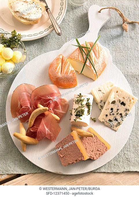 Cheese platter with raw ham and butter balls for brunch