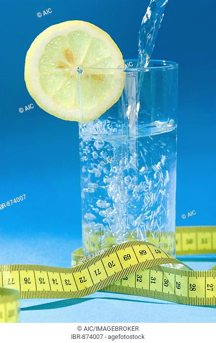 Glas with slice of lemon and a measuring tape