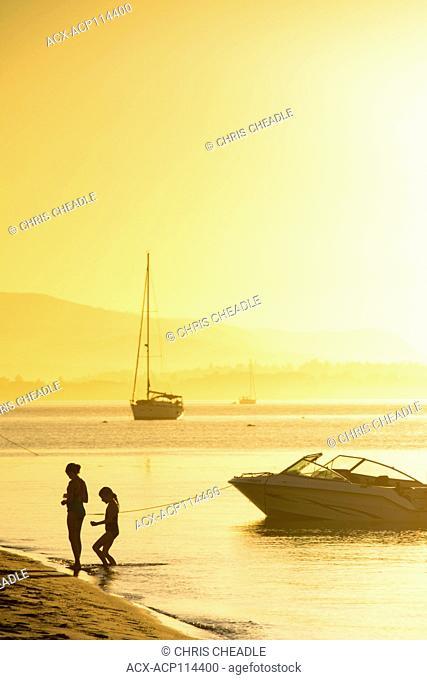 Girls ashore on beach at Sidney Island, Gulf Islands National Park Reserve, British Columbia, Canada
