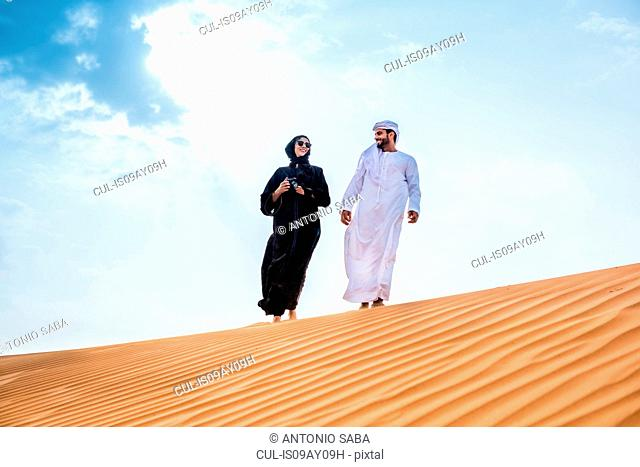 Couple wearing traditional middle eastern clothes walking on desert dune, Dubai, United Arab Emirates