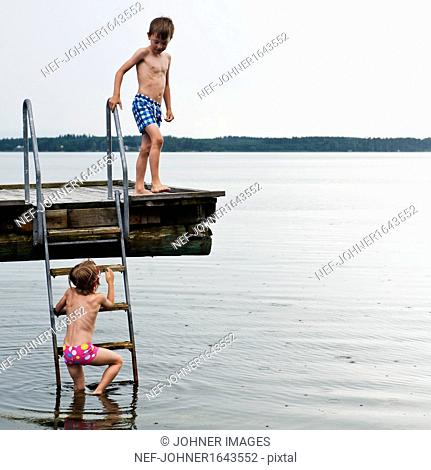 Two boys on jetty by sea