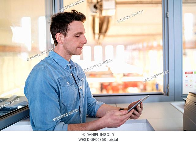 Businessman using tablet at the window with factory background