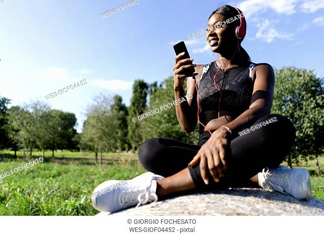 Young athlete sitting on straw bale, listening music with smartphone and headphones