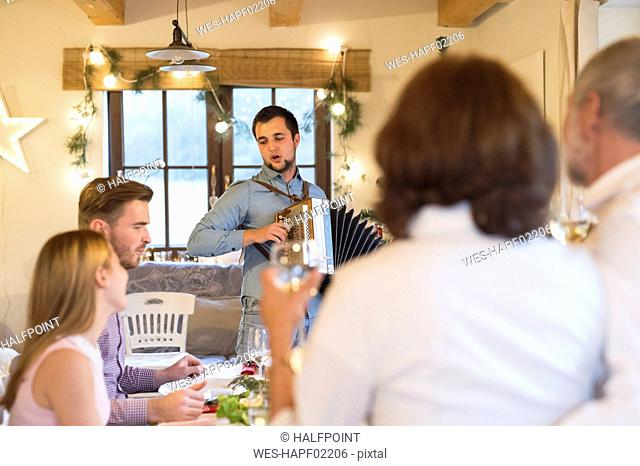 Young man playing accordion for family at Christmas dinner table