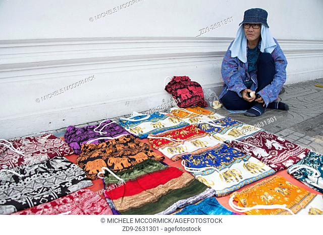 A street vendor sells colorful pants with local designs