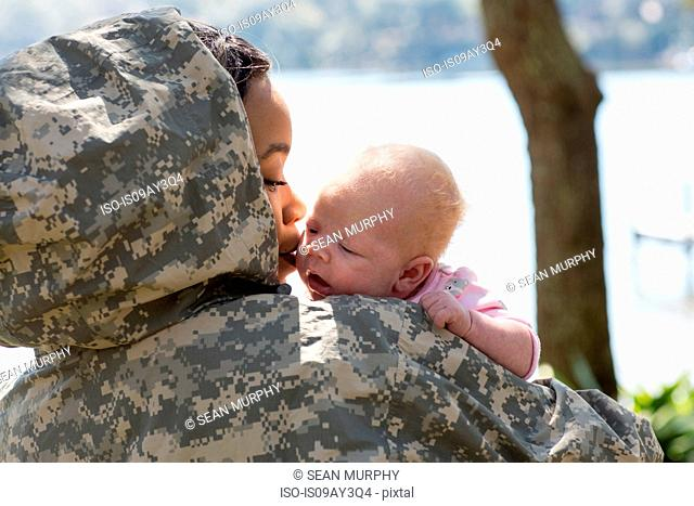 Over shoulder view of female soldier and baby daughter at military air force base