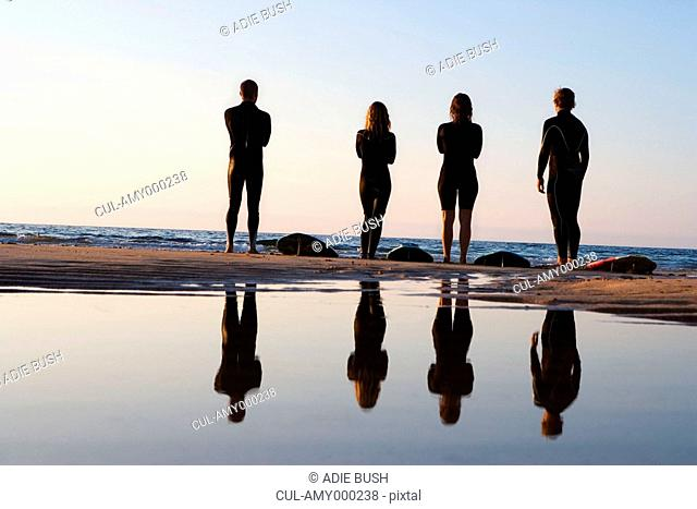 Four people standing on the beach with surfboards