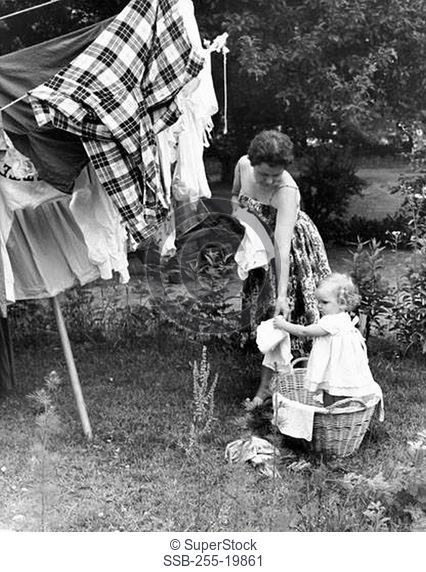 Daughter helping her mother hang clothes on a clothesline