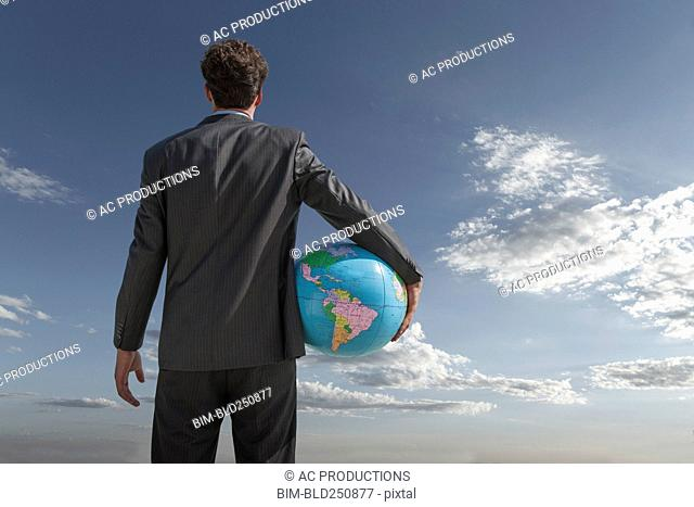 Caucasian businessman holding globe in sky