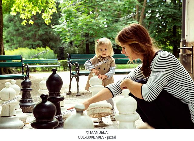 Mother and toddler daughter playing with giant chess in park