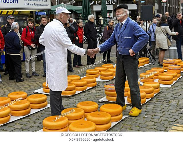 A cheese merchant, left, and a farmer, right, bargain over the price of Gouda cheese by each slapping the other's hand at the cheese market, Gouda, Netherlands