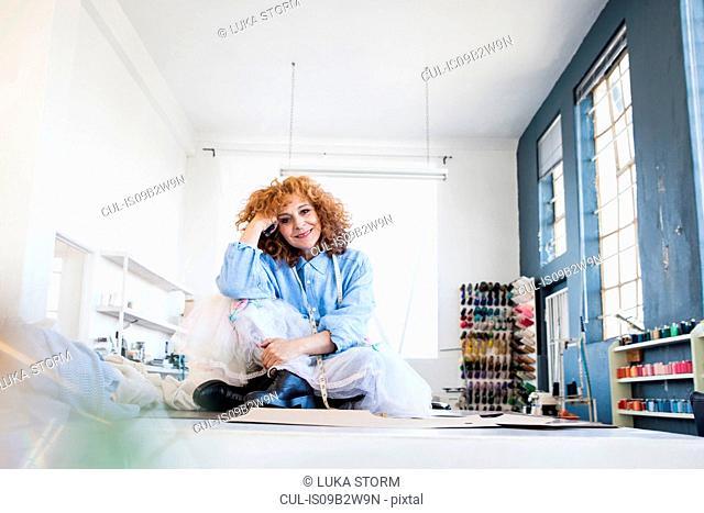 Fashion designer sitting cross-legged on desk looking at camera smiling
