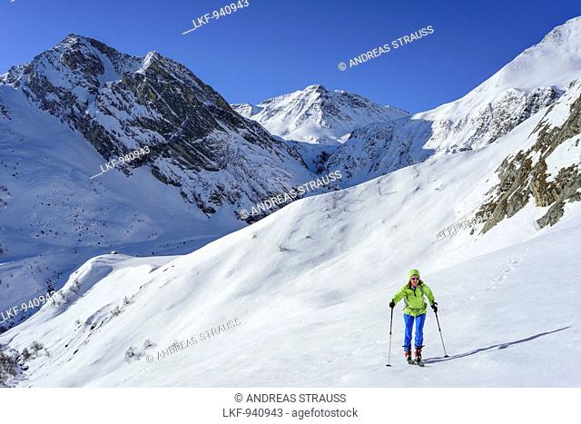 Woman back-country skiing ascending towards Monte Salza, in background Monte Pence and Buc Faraut, Monte Salza, Valle Varaita, Cottian Alps, Piedmont, Italy