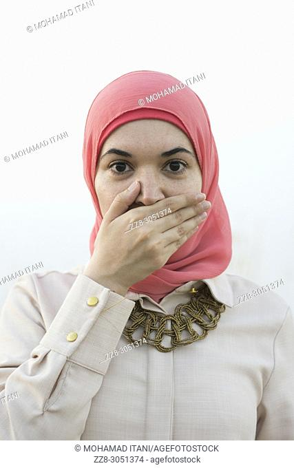 Muslim woman covering mouth with hand