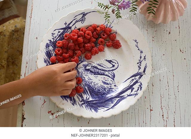 Hand reaching for raspberries on plate