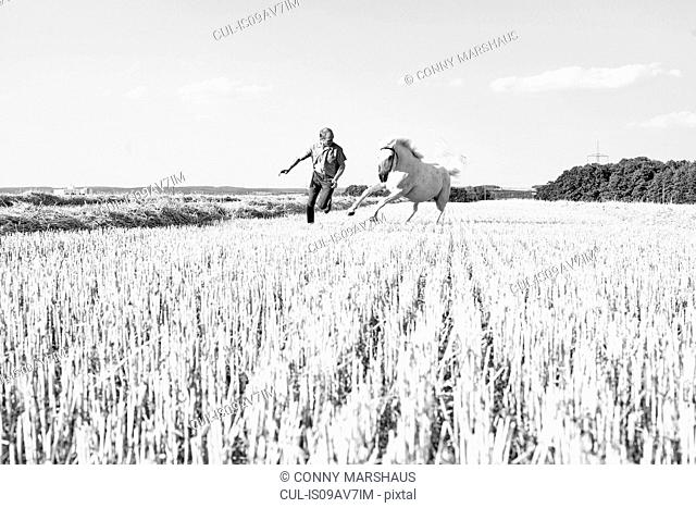 B&W image of man training galloping horse in field