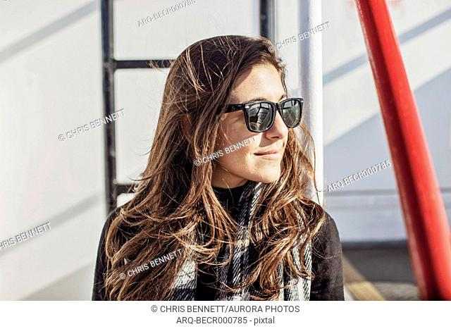 Portrait of smiling attractive young woman wearing sunglasses on ferryÂ