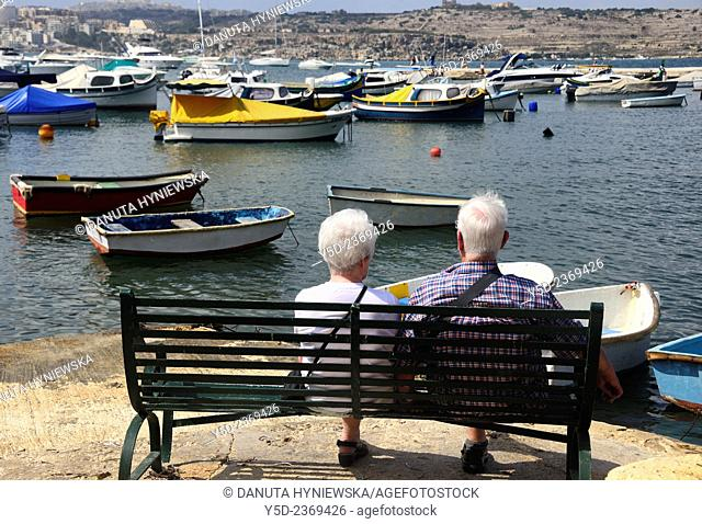 mature couple sitting at the bench admiring view of St Paul Bay, Malta
