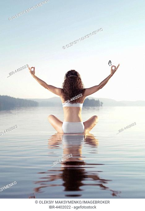 Woman meditating with a butterfly on her hand, on a floating platform in calm water of a lake in morning light, yoga meditation