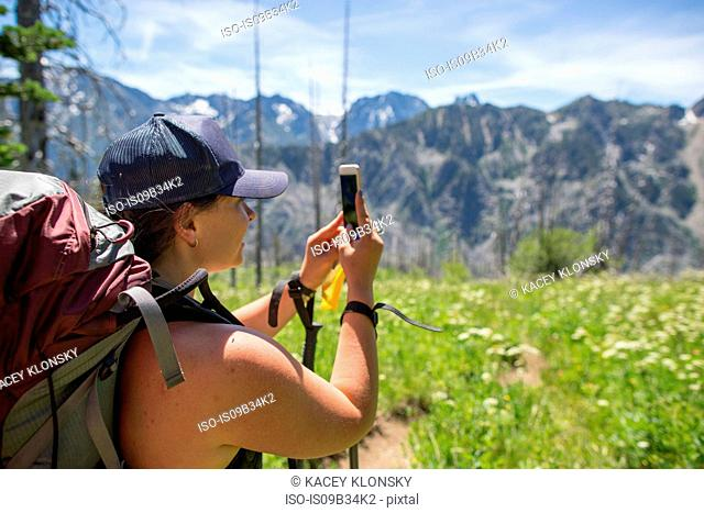 Hiker taking photograph of view, Enchantments, Alpine Lakes Wilderness, Washington, USA