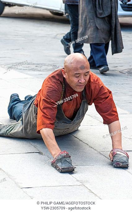 A pilgrim prostrating himself around the Barkhor circuit in Lhasa, Tibet
