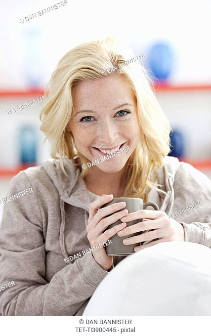 Young woman relaxing at home and holding mug