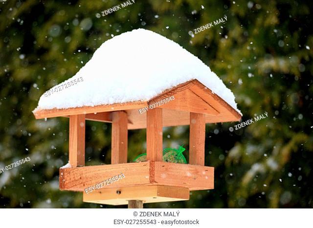 simple homemade wooden bird feeder, birdhouse installed on winter garden in snowy day