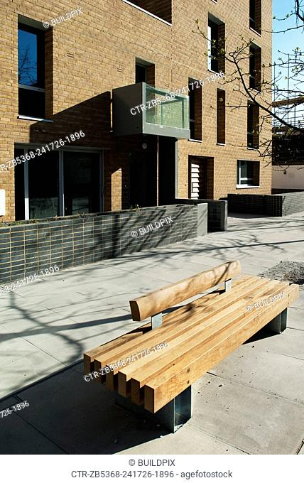Wooden bench on a pavement outside a housing development, Bow Cross, East London, UK