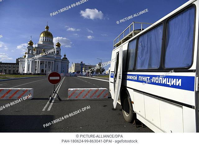 24 June 2018, Russia, Saransk: Soccer, World Cup 2018: A police cordon and two buses face the Fifa Fanfest in front of the Russian Orthodox Cathedral of the...
