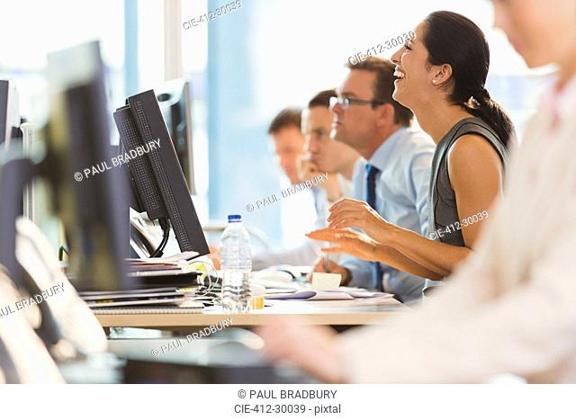 Laughing businesswoman working at computer in office