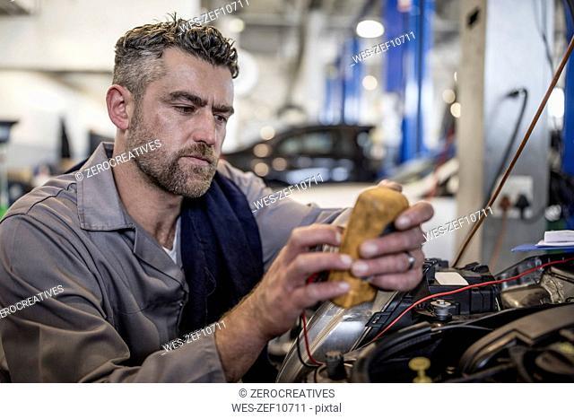 Car mechanic in a workshop using diagnostic equipment