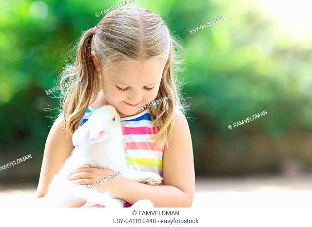 Child playing with white rabbit. Little girl feeding and petting white bunny. Easter celebration. Egg hunt with kid and pet animal