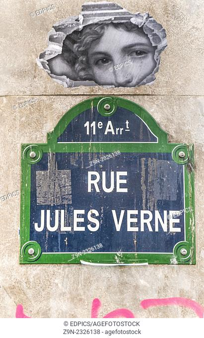 parisian street signpost -rue jules verne- above it the face of an angel, paris, ile de france, france