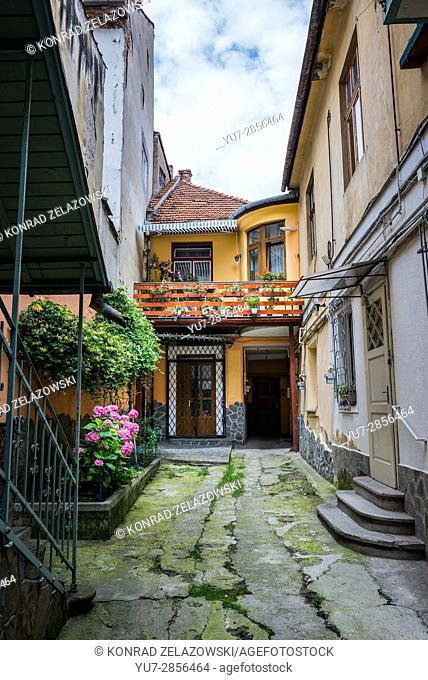 Courtyard of tenement houses near Republic Street, main pedestrian thoroughfare full of shops and restaurants in Brasov, Romania
