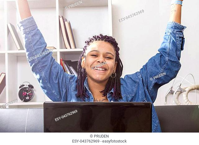 female young hispanic american, african descent, celebrating with the computer