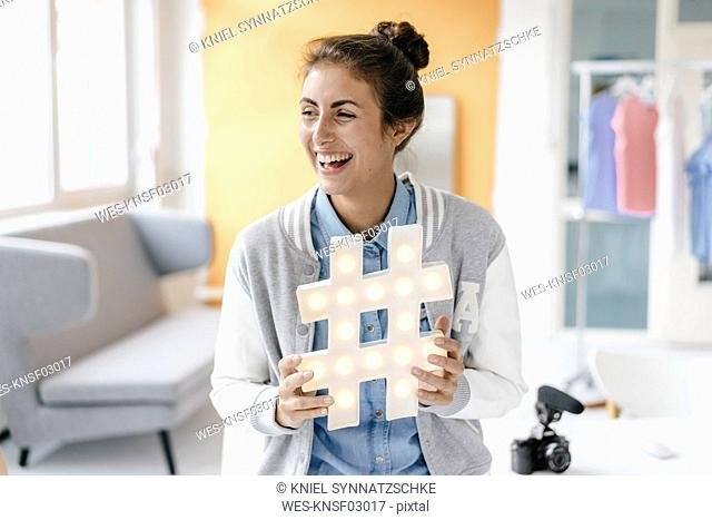 Laughing young woman holding hashtag sign in studio