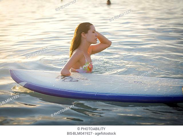 Mixed race amputee with surfboard in ocean