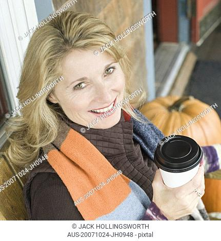 Portrait of a mature woman holding a cup and smiling