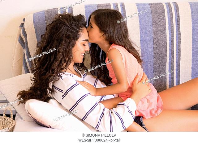 Little girl kissing teenage sister
