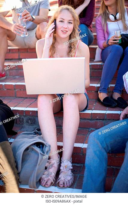 Female student on steps using laptop on cell phone