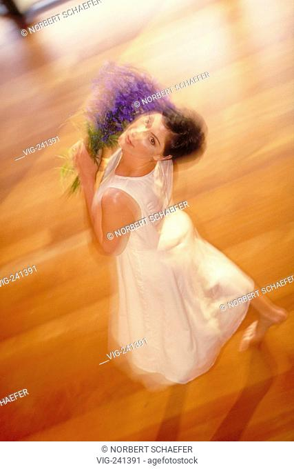portrait, young woman with short brown hair in white shining sleeping gown hovers bare feeted with a buncht of lilac over the parquet of the living room -...