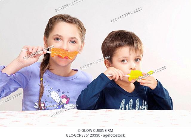 Boy and his sister eating candies