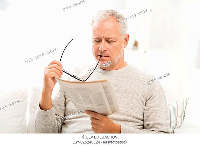 leisure, information, people and mass media concept - senior man in glasses reading newspaper at home